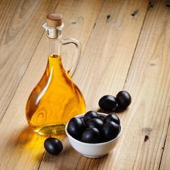 Bottiglia di olio d'oliva e olive in ciotola su legno