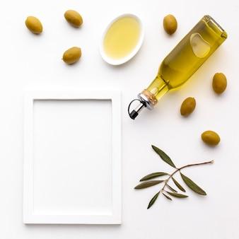 Bottiglia di olio d'oliva e piattino con olive gialle e cornice mock-up