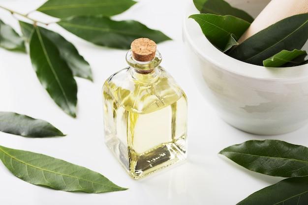 Bottiglia di olio di alloro con foglie e mortaio