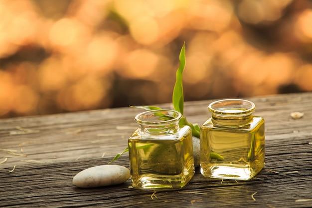 Bottiglia di olio essenziale aroma o spa e congedo verde naturale sul tavolo di legno