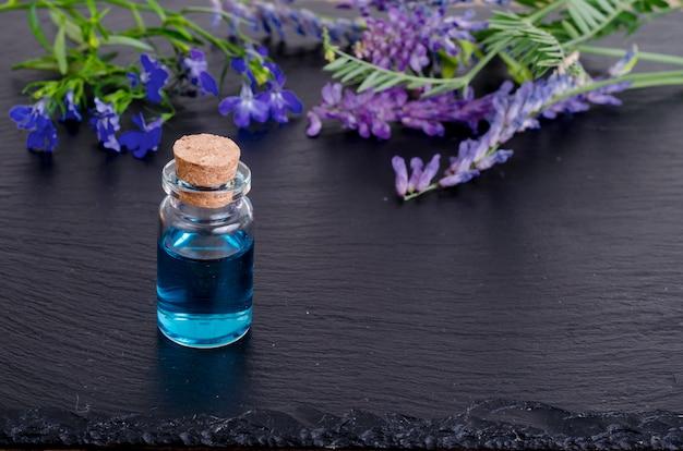 Bottiglia di olio essenziale blu con fiori freschi.
