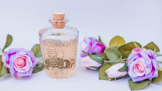 Bottiglia di olio essenziale e fiori finti su superficie bianca
