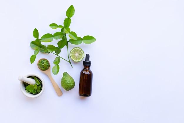 Bottiglia di olio essenziale e lime fresco di kaffir o di bergamotto con foglie
