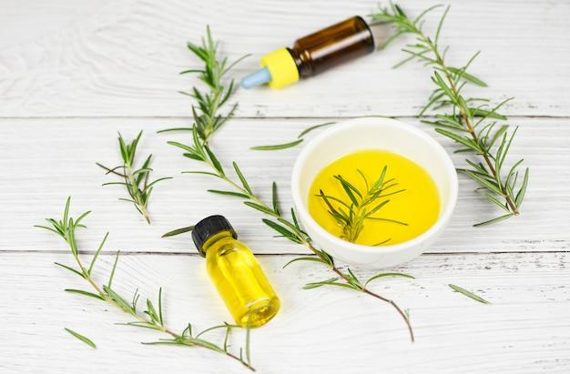 Bottiglia di olio essenziale ingredienti spa naturali olio di rosmarino per aromaterapia e foglie di rosmarino su fondo di legno - cosmetici biologici con estratti di erbe