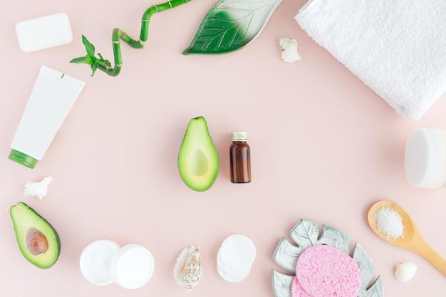 Bottiglia di olio, foglie verdi e bambù, asciugamano bianco e avocado fresco su rosa, flatlay