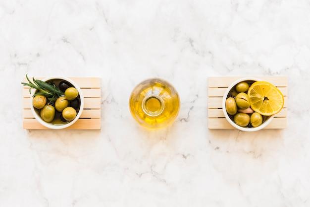 Bottiglia di olio tra le due ciotole di oliva con rosmarino e fettina di limone