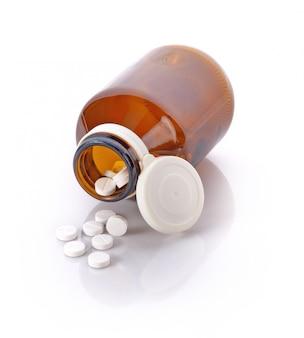 Bottiglia di pillola che rovescia le pillole sopra per sorgere isolato su un fondo bianco