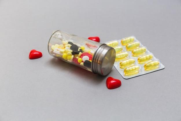 Bottiglia di pillole e cuore rosso su sfondo grigio