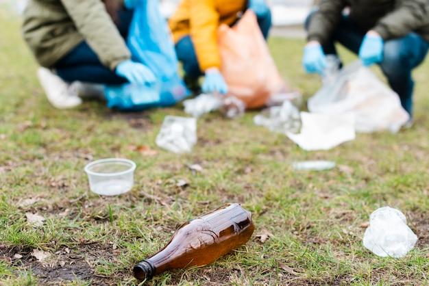 Bottiglia di plastica a terra con bambini sfocati