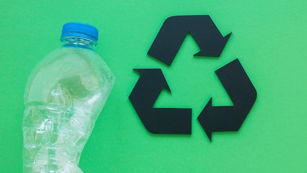 Bottiglia di plastica accanto al segno di riciclaggio