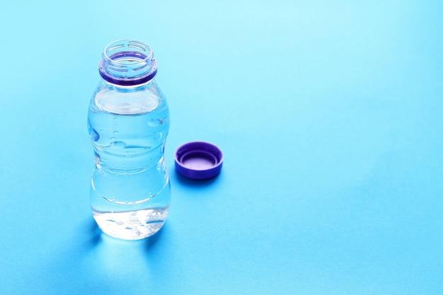 Bottiglia di plastica con acqua sul blu.