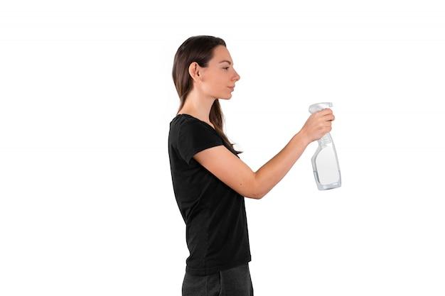 Bottiglia di plastica dello spruzzo della tenuta della giovane donna con liquido detergente. concetto di pulizie di primavera. disinfezione