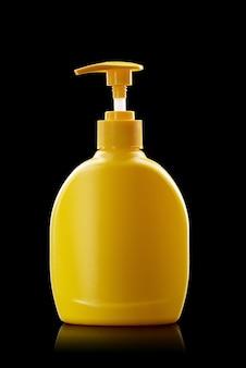 Bottiglia di plastica gialla della pompa isolata su una priorità bassa nera. distributore di disinfezione mani, concetto di igiene personale.