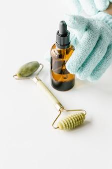 Bottiglia di plastica marrone per cosmetici liquidi nelle mani della donna in guanti verdi, rullo di massaggio giada verde sul tavolo bianco