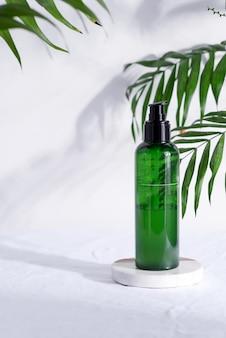 Bottiglia di plastica verde con lozione naturale per la pelle pulita su uno sfondo di tessuto bianco con foglie tropicali verde.
