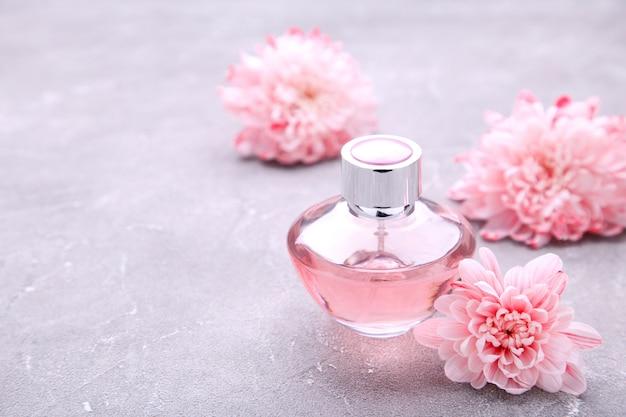 Bottiglia di profumo con fiori su cemento grigio