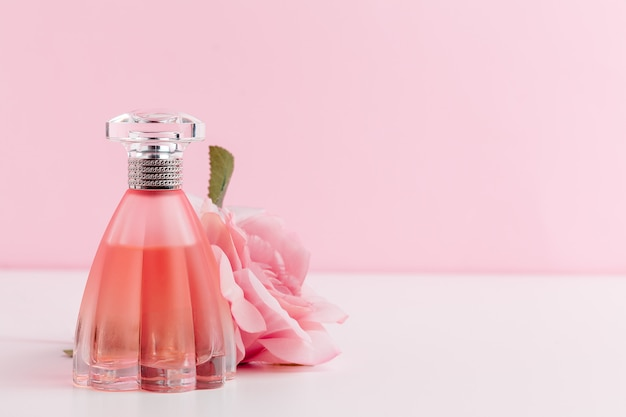Bottiglia di profumo con fiori su colore