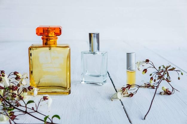 Bottiglia di profumo con fiori su un tavolo di legno bianco