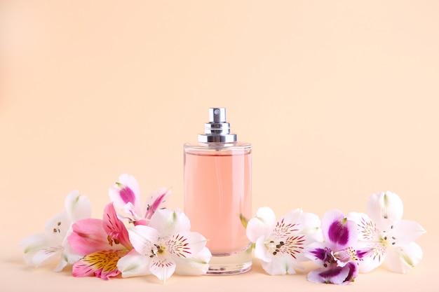 Bottiglia di profumo con fiori sul beige