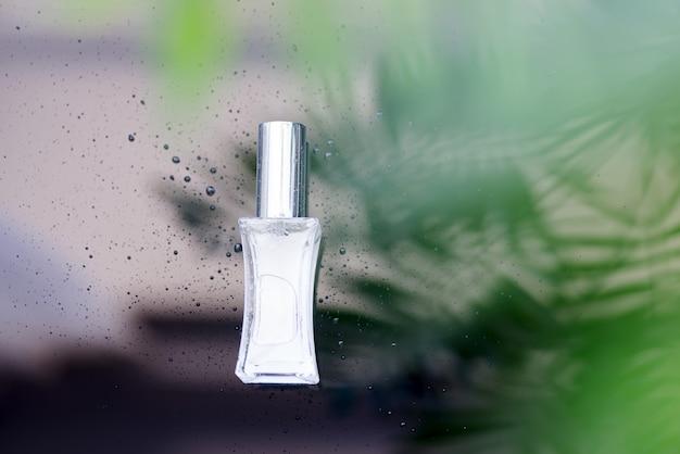 Bottiglia di profumo con foglie tropicali verdi.