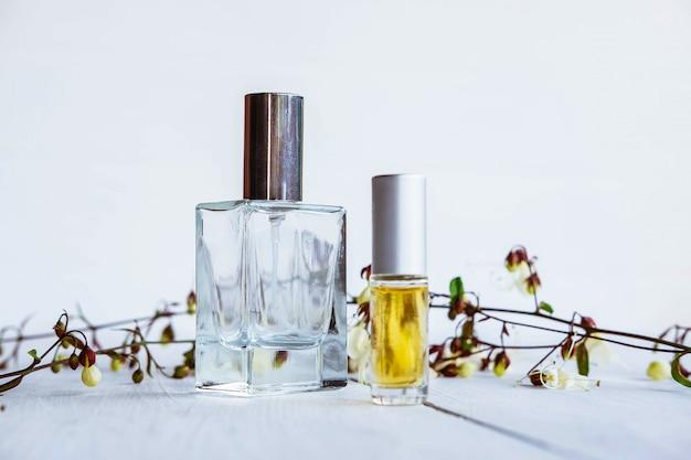 Bottiglia di profumo con i fiori su un fondo di legno bianco