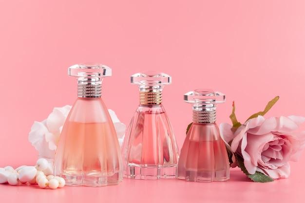 Bottiglia di profumo con rose su tessuto rosa
