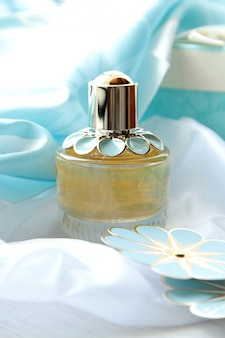 Bottiglia di profumo di vista frontale con un fiore di carta blu