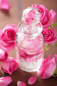 Bottiglia di profumo e fiori rosa rosa. aromaterapia termale