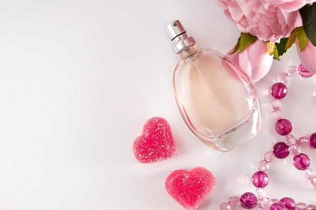 Bottiglia di profumo, fiori e cuori su una luce