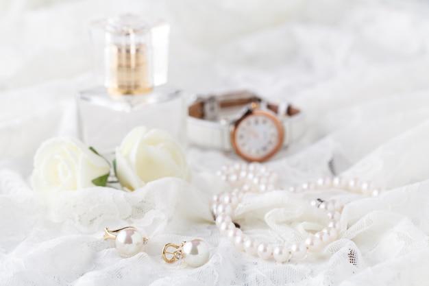 Bottiglia di profumo in vetro sul tavolo da toeletta da donna con collana e lacci di perle schic squallide