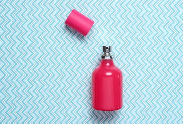 Bottiglia di profumo rossa sulla vista blu e superiore creativa