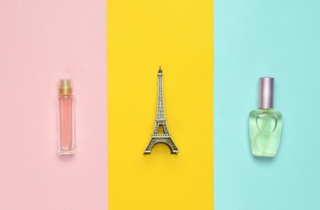Bottiglia di profumo, una statuetta della torre eiffel su uno sfondo di carta multicolore, vista dall'alto, minimalismo