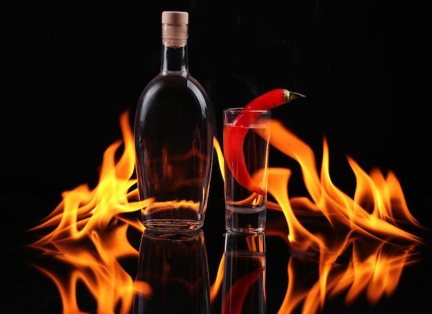Bottiglia di tequila in fiamme e un bicchiere di peperoncino