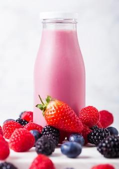 Bottiglia di vetro con frullato di bacche fresche d'estate