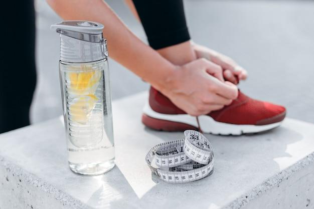 Bottiglia di vetro del primo piano di acqua con la misura di nastro e del limone
