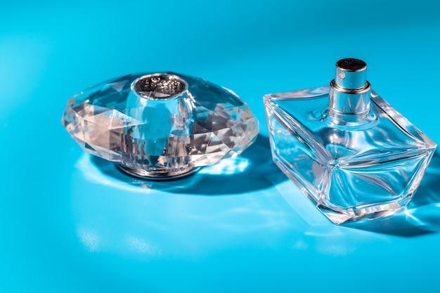 Bottiglia di vetro del profumo su fondo blu-chiaro. profumo