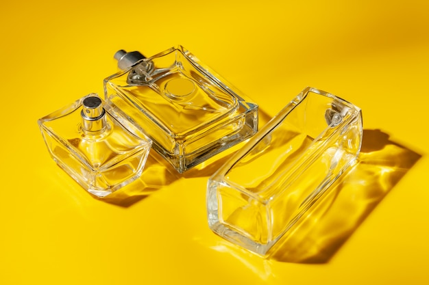 Bottiglia di vetro del profumo su fondo giallo-chiaro. profumo