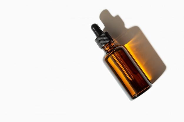 Bottiglia di vetro del siero o dell'olio essenziale con la pipetta isolata su fondo bianco. copia spazio