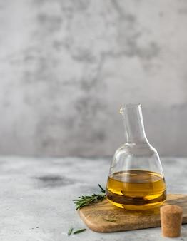 Bottiglia di vetro di olio extra vergine di oliva con un ramo di superficie grigio rosmarino,