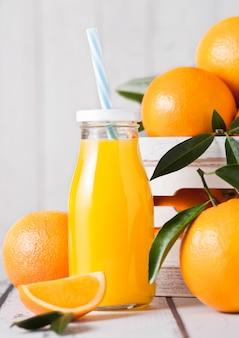 Bottiglia di vetro di succo d'arancia fresco organico con arance crude sulla scatola di legno bianca