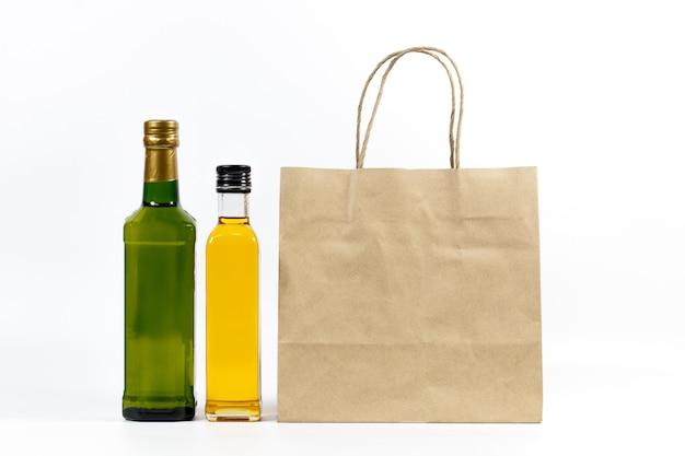 Bottiglia di vetro gialla e verde con il sacco di carta isolato su un fondo bianco.