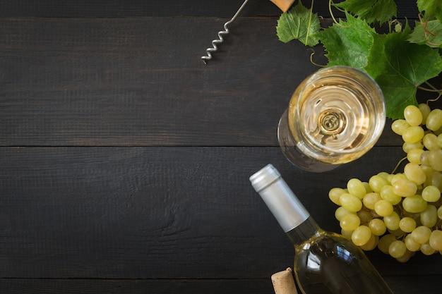 Bottiglia di vino bianco con bicchiere di vino, uva matura sul tavolo di legno nero.
