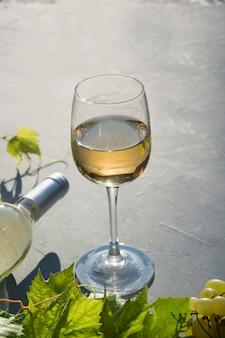 Bottiglia di vino bianco con bicchiere di vino, uva matura sul tavolo grigio cemento.