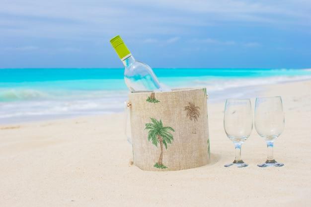 Bottiglia di vino bianco e due bicchieri sulla spiaggia di sabbia esotica