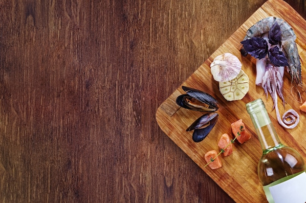 Bottiglia di vino bianco e salsa rossa sul tagliere e tavolo in legno, con set di frutti di mare - cozze, gamberi, polpo, basilico e piccoli pezzi di salmone alle erbe