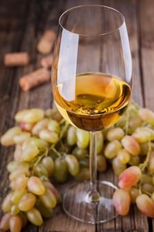 Bottiglia di vino bianco, uva e tappi di sughero