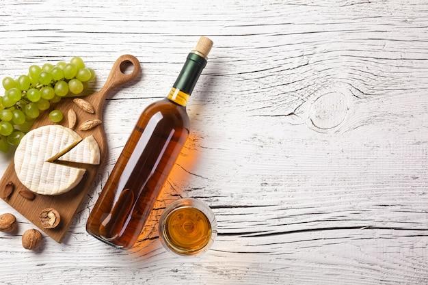 Bottiglia di vino bianco, uva, formaggio e bicchiere di vino sul bordo di legno bianco