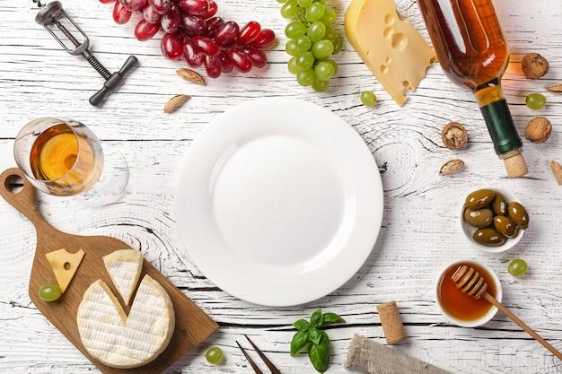 Bottiglia di vino bianco, uva, miele, formaggio, bicchiere da vino e piastra su tavola di legno bianca