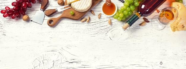 Bottiglia di vino bianco, uva, miele, formaggio e bicchiere di vino sul bordo di legno bianco