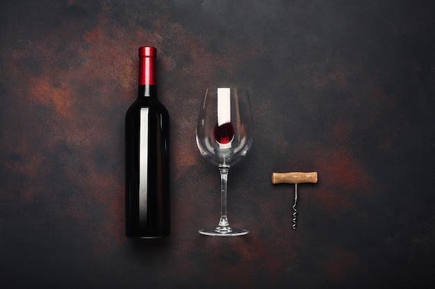 Bottiglia di vino, cavatappi e bicchiere di vino su sfondo arrugginito